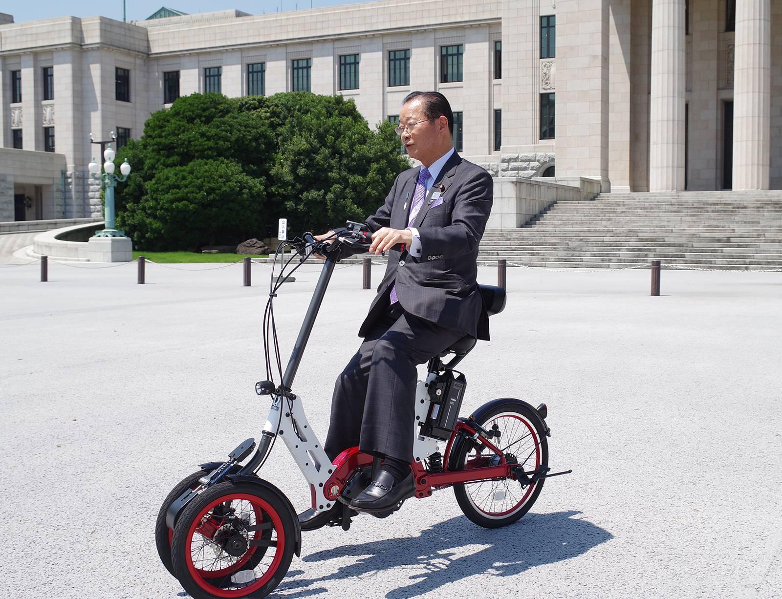展示ブースにあった試乗バイクを試す河村建夫衆議院議員(自転車議連会長代行)