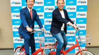 サービスで使用するシェアサイクルに乗る福岡高島市長(左)とメルカリの小泉文明社長(右)